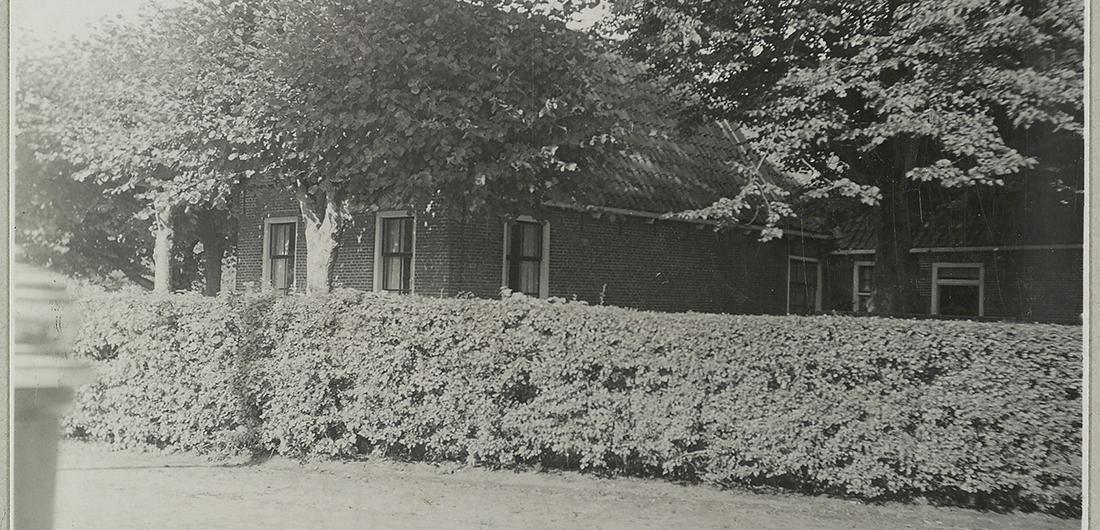 1933 Korte gevel en lange gevel achter haag en bomen in Garijp/Garyp (Friesland). Foto van Atema, L., Collectie Rijksdienst voor het Cultureel Erfgoed, objectnummer OF-02421
